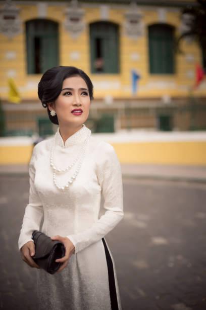 Vietnamese woman wearing Classic Ao dai holding wallet in the saigon street
