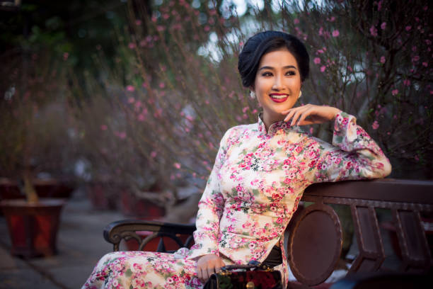 Vietnamese woman wearing Classic Ao dai sitting beside Peach blossom flowers