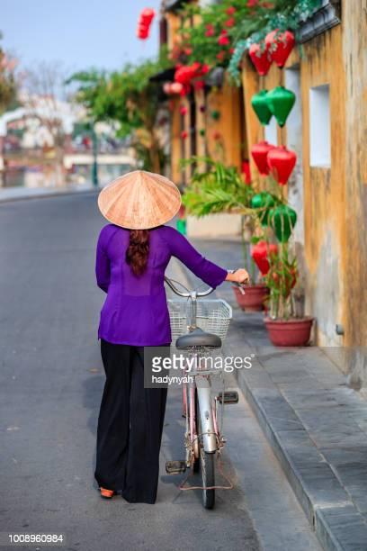 femme vietnamienne avec un vélo, la vieille ville de hoi an ville, vietnam - vietnamien photos et images de collection