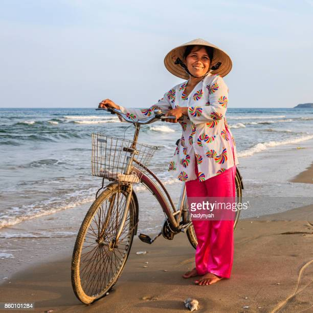 Vietnamese woman with a bicycle on the beach, Vietnam