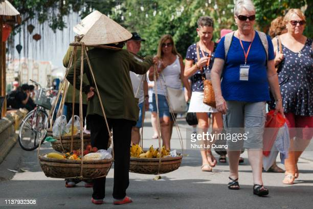 vietnamese woman with conical hat carries a yoke on her shoulder in hoi an old town street - poor service delivery stock pictures, royalty-free photos & images
