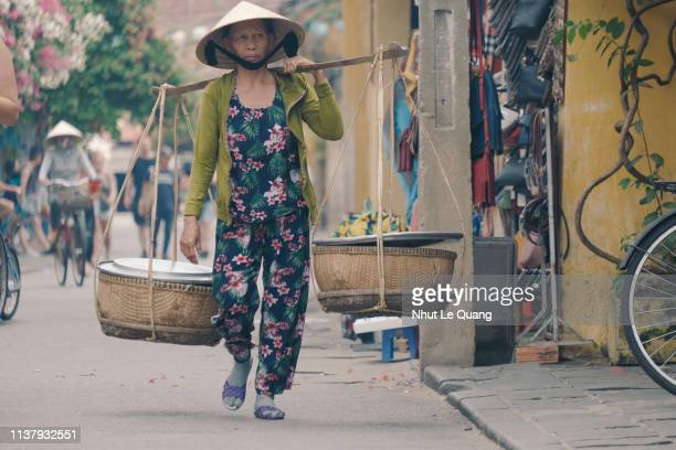 vietnamese woman with conical hat carries a yoke on her shoulder - poor service delivery stock pictures, royalty-free photos & images