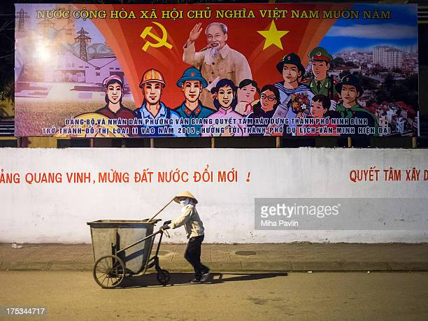 CONTENT] Vietnamese woman with conical hat pushing trash cart in front of billboard with communist slogans / propaganda nightime