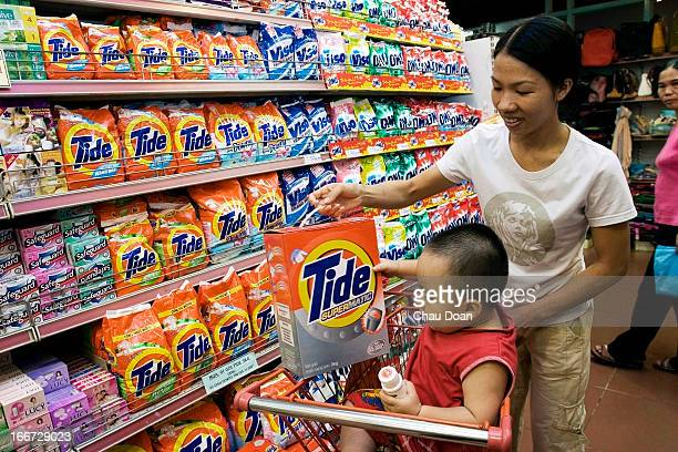 Vietnamese woman with her litle boy add a box of Tide a Procter Gamble product to their shopping cart at the Tax Trade Center in Ho Chi Minh City