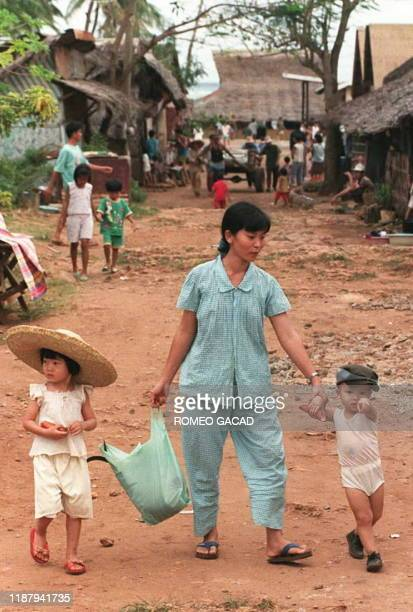 Vietnamese woman with her two children walk in the camp at Puerto Princesa, Philippines 11 January which houses more than 2,000 disqualified...