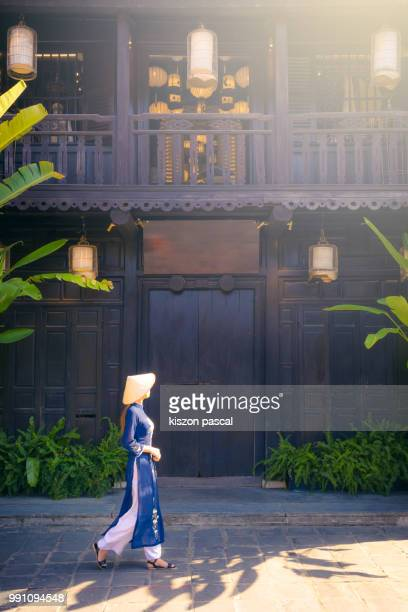 vietnamese woman with traditional clothes and conical hat visiting the old town of hoi an in vietnam , southeast asia - vietnam stock pictures, royalty-free photos & images