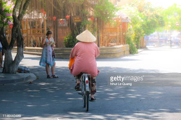 vietnamese woman with traditional conical hat on a bicycle on a road in hoi an old town - poor service delivery stock pictures, royalty-free photos & images