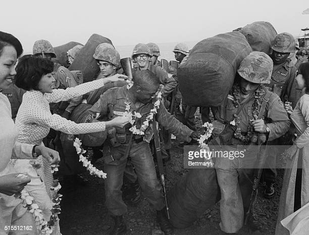 Vietnamese women adorn soldiers of the US 25th Division with peace leis upon their arrival to Vung Tau South Vietnam