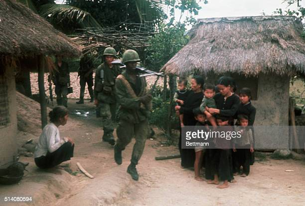 Vietnamese women and children huddle together as US soldiers from a 3rd Brigade 25th Division task force enter their village on May 12 1967