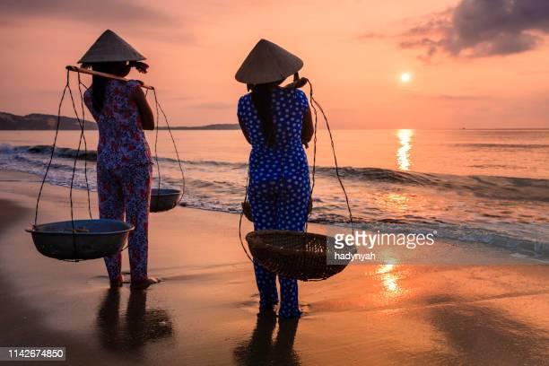 vietnamesische frauen, die früchte am strand, vietnam - vietnam stock-fotos und bilder