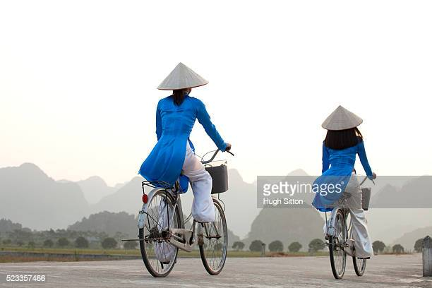 vietnamese women cycling in typical landscape near hanoi. vietnam - hugh sitton stock pictures, royalty-free photos & images