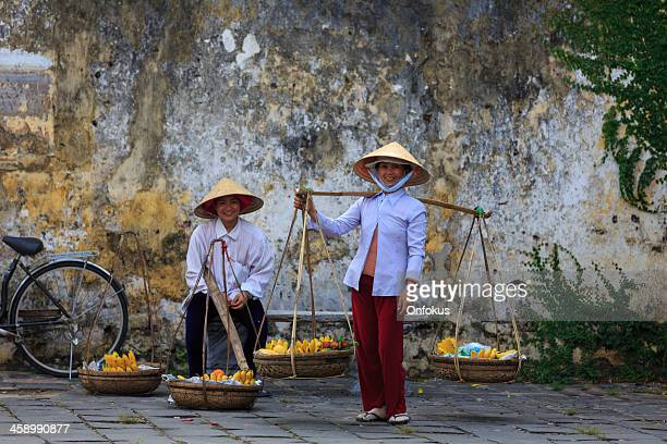 vietnamese women holding fruits baskets, hoi an, vietnam - asian style conical hat stock pictures, royalty-free photos & images