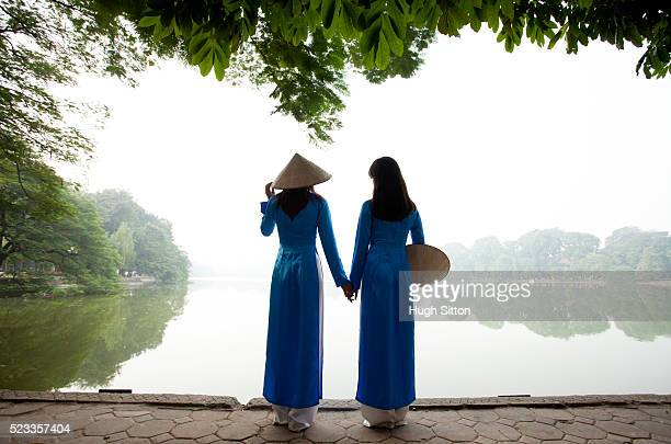 vietnamese women in traditional costume. ho kiem lake. hanoi. - hugh sitton stock pictures, royalty-free photos & images