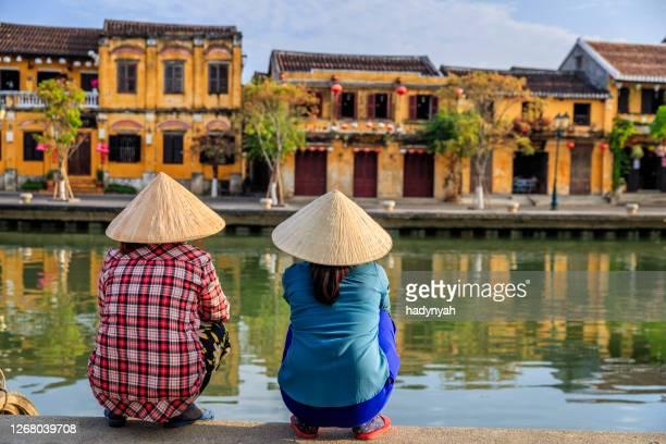 femmes vietnamiennes regardant la vieille ville dans la ville d'hoi an, vietnam - vietnamien photos et images de collection