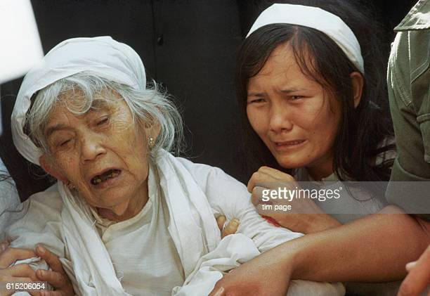 Vietnamese women mourn for a dead Catholic priest wearing traditional white clothing