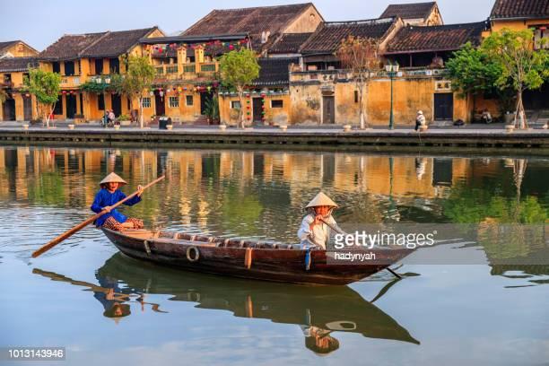 donne vietnamite che remare nel centro storico della città di hoi an, vietnam - vietnam foto e immagini stock