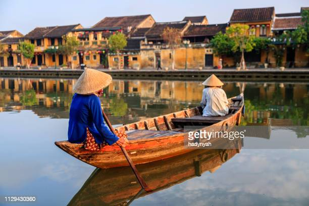 vietnamese women paddling in old town in hoi an city, vietnam - vietnam stock pictures, royalty-free photos & images