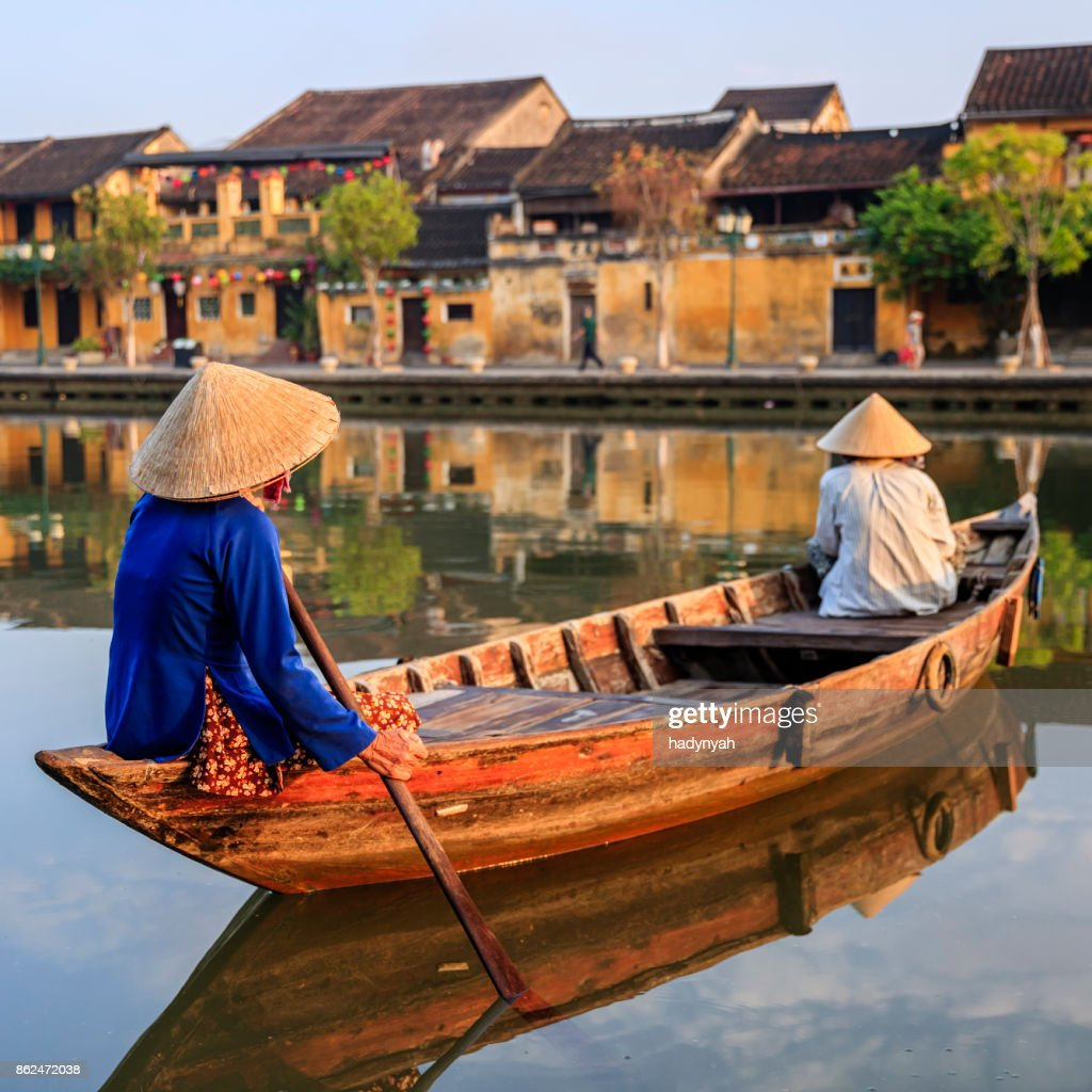 Vietnamese women paddling in old town in Hoi An city, Vietnam : Stock Photo
