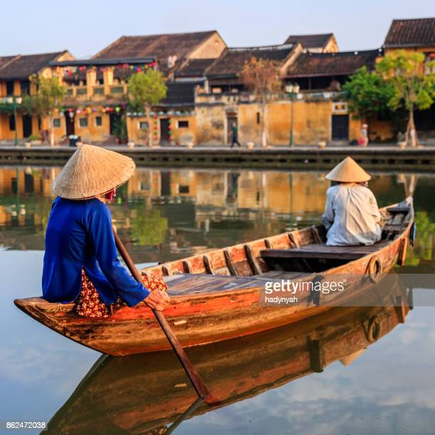 vietnamese women paddling in old town in hoi an city, vietnam - traditionally vietnamese stock pictures, royalty-free photos & images