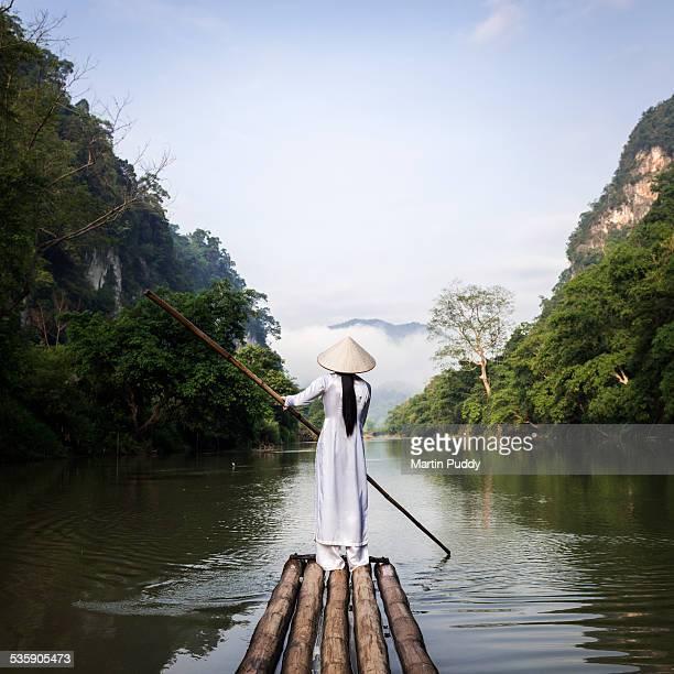 Vietnamese women punting bamboo raft along river