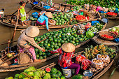 Vietnamese women selling fruits on floating market, Mekong River Delta, Vietnam