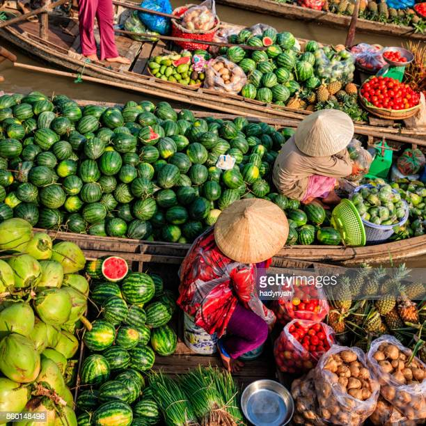 vietnamese women selling fruits on floating market, mekong river delta, vietnam - traditionally vietnamese stock pictures, royalty-free photos & images