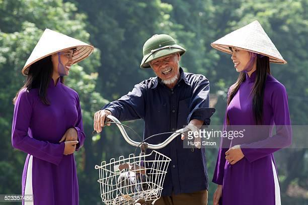 vietnamese women talking to older man with bicycle. vietnam - hugh sitton stock-fotos und bilder