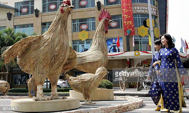 Vietnamese women walk past rooster models a zodiac in lunar calendar installed at downtown of Ho Chi Minh City 07 February 2005 as part of...