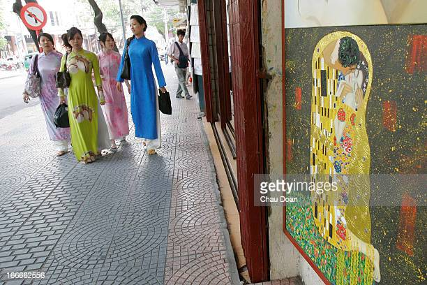 Vietnamese women wearing the traditional Ao Dai pass by a gallery selling copied paintings Copying paintings has been a good business for some...