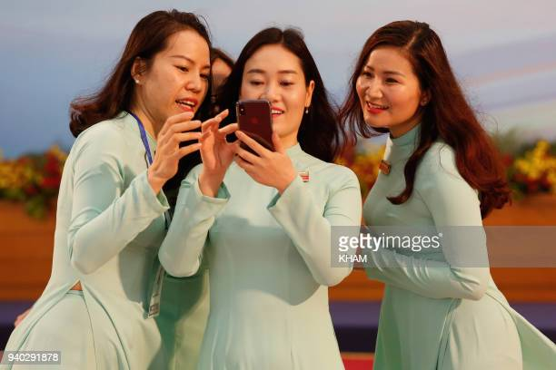 Vietnamese women wearing the traditional long dress 'ao dai' take a selfie photo at the National Convention Center during the Greater Mekong...
