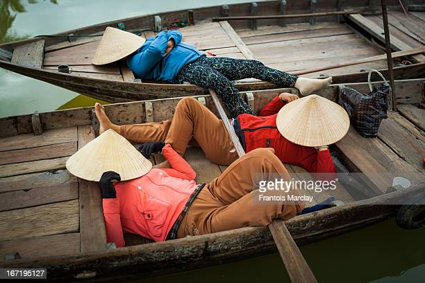 CONTENT] Vietnamese women with their face covered with a traditional conical leaf hat sleeping on row boats during a sunny afternoon in Hoi An