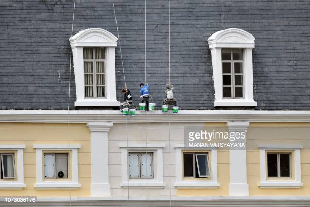 Vietnamese workers paint the exterior facade of a commercial building in Hanoi on December 14 2018