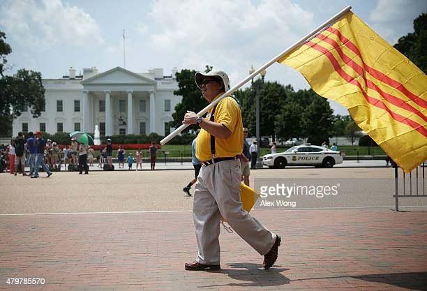 Vietnamese-American activist holds a South Vietnam flag as he participates in a protest outside the White House as U.S. President Barack Obama meets...