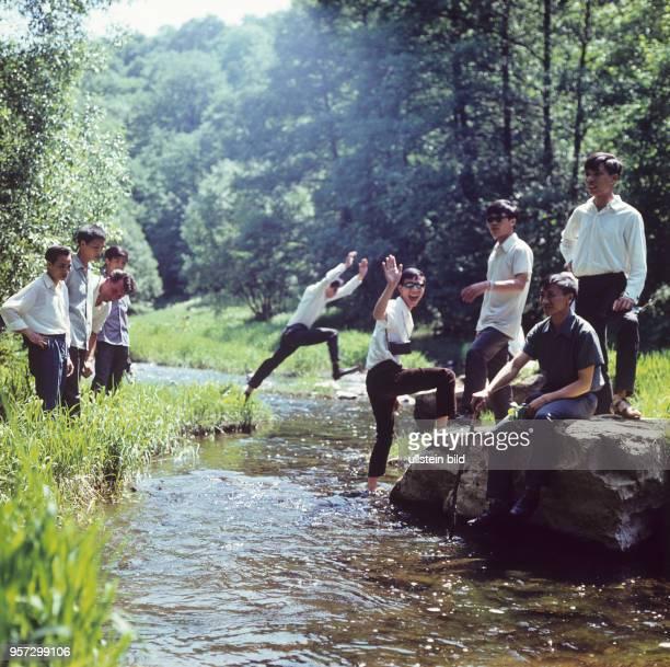 Vietnamesische Gastarbeiter die im VEBKabelwerk Oberspree Berlin eine Ausbildung absolvieren an einem Bach bei einem Urlaub im Harz aufgenommen im...
