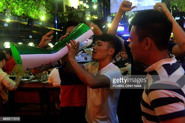 VietnamhealthsocialalcoholFEATURE by Cat Barton This picture taken on December 13 2014 shows a man drinking beer from a tower as his friends look on...