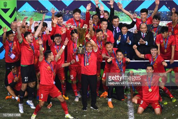 Vietnam's coach Park Hangseo holds the trophy as the players and Vietnam's Prime Minister Nguyen Xuan Phuc celebrate after winning the AFF Suzuki Cup...