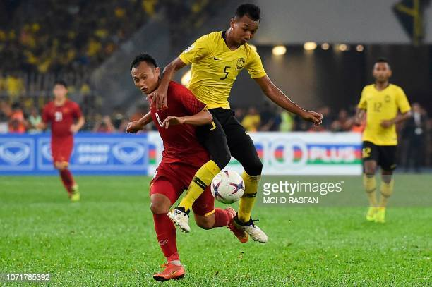 Vietnam's defender Nguyen Trong Hoang and Malaysia's defender Adam Nor Azlin fight for the ball during the AFF Suzuki Cup 2018 final football match...