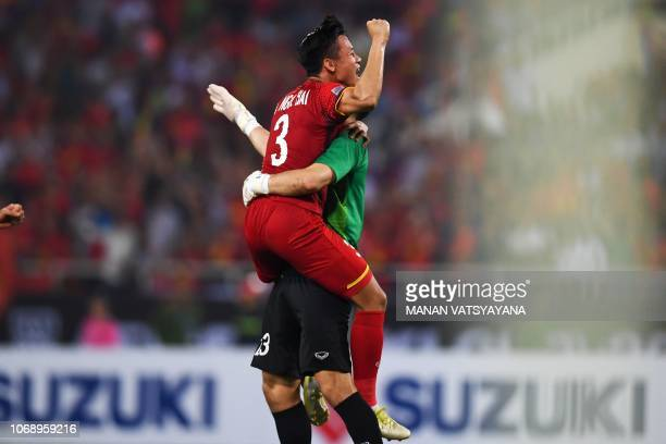 Vietnam's defender Que Ngoc Hai and goalkeeper Dang Van Lam celebrate at the end of the second leg of the AFF Suzuki Cup 2018 semifinal football...