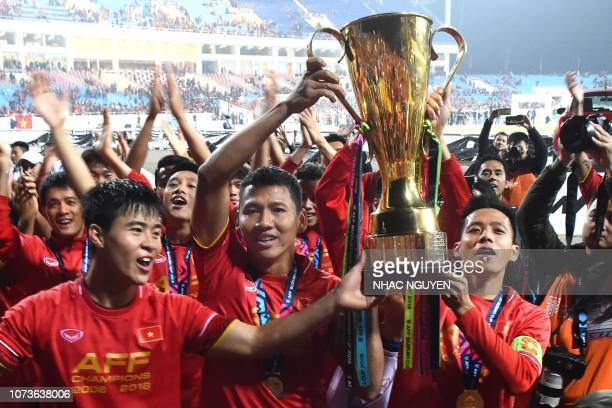 Vietnam's forward Nguyen Anh Duc and teammates hold the trophy as they celebrate after winning the AFF Suzuki Cup 2018 final football match between...