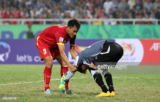 Vietnam's goalkeeper Tran Nguyen Manh is conforted by teammate Le Phuoc Tu after he made an error allowing Indonesia to score a goal during their AFF...