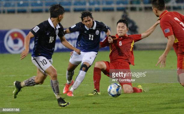 Vietnam's Luong Xuan Truong fights for the ball with Cambodia's Chan Vathanaka and Keo Sokpheng during the AFC Asian 2019 Cup qualifier against...
