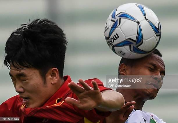 Vietnam's Luong Xuan Truong fights for the ball with East Timor's Jorge Sabas Victor during their men's football Group B round match at the 29th...