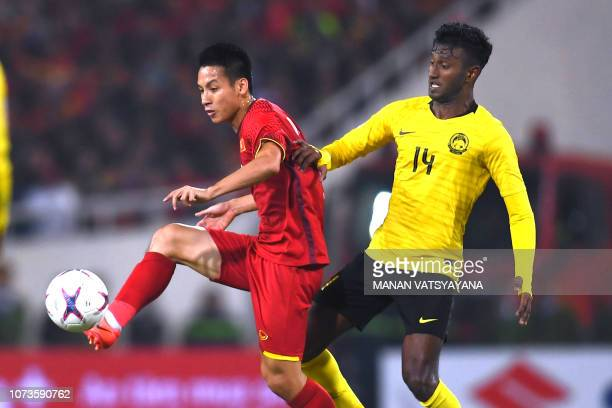 Vietnam's midfielder Do Hung Dung and Malaysia's midfielder Syamer Kutty Abba fight for the ball during the AFF Suzuki Cup 2018 final football match...