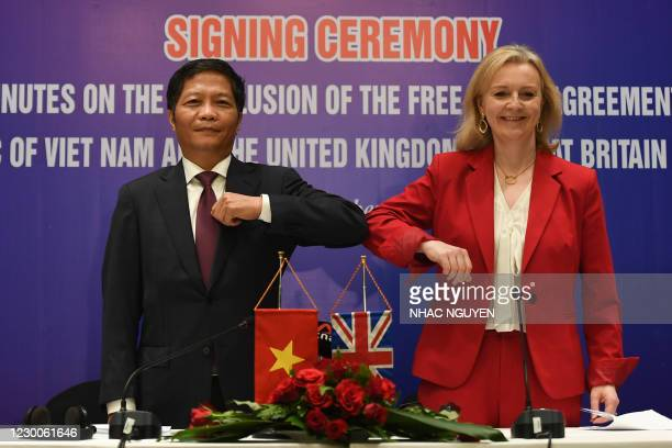 Vietnam's Minister of Industry and Trade Tran Tuan Anh and Britain's International Trade Secretary Liz Truss elbow bump after signing a free trade...