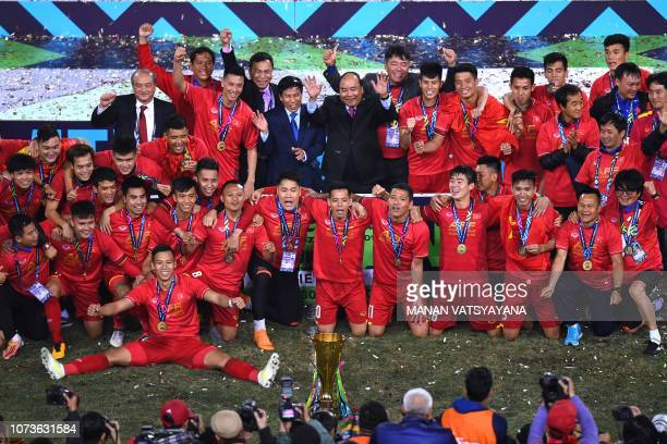 Vietnam's players and Vietnam's Prime Minister Nguyen Xuan Phuc celebrate in front of the trophy after winning the AFF Suzuki Cup 2018 championship...