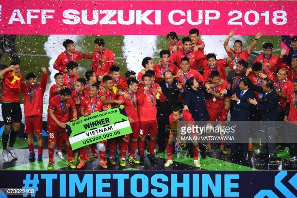 Vietnam's players celebrate with Vietnam's Prime Minister Nguyen Xuan Phuc after winning the AFF Suzuki Cup 2018 championship trophy at the AFF...