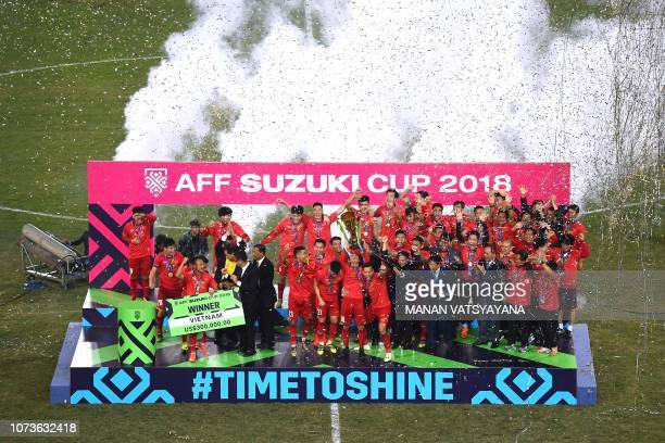 Vietnam's players hold the trophy as they celebrate after winning the AFF Suzuki Cup 2018 final football match between Vietnam and Malaysia at the My...