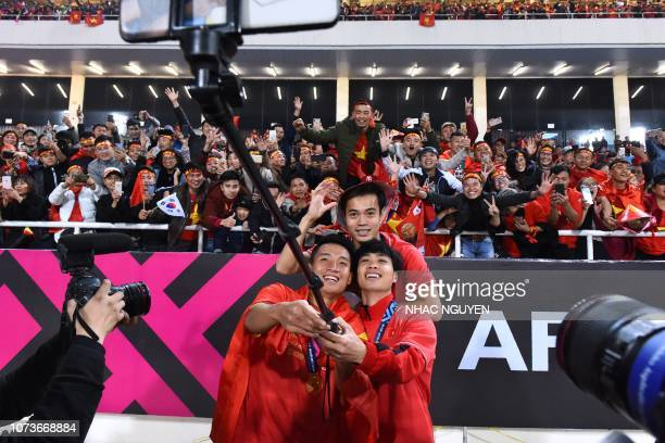 Vietnam's players pose for a selfie after winning the AFF Suzuki Cup 2018 final football match between Vietnam and Malaysia at the My Dinh Stadium in...