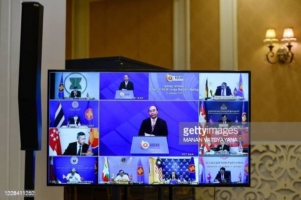 Vietnam's Prime Minister Nguyen Xuan Phuc and Foreign ministers from ASEAN countries are seen on a television screen during the opening ceremony of...