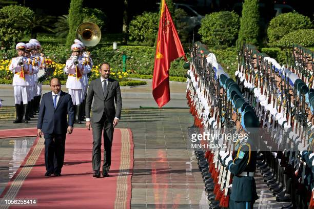 TOPSHOT Vietnam's Prime Minister Nguyen Xuan Phuc and his French counterpart Edouard Philippe inspect the guard of honor during a welcoming ceremony...